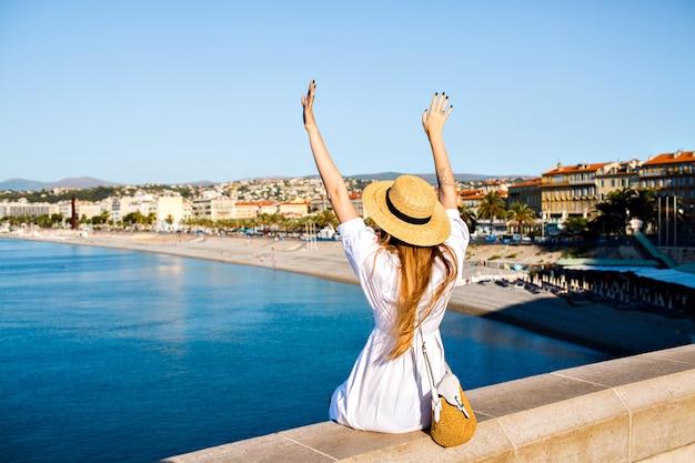 Feliz mujer elegante posando de nuevo, puso su mano en el aire y disfrutando de una vista increíble