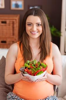 Feliz mujer embarazada comiendo ensalada saludable