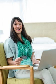 Feliz mujer embarazada de compras en línea en su computadora portátil en casa