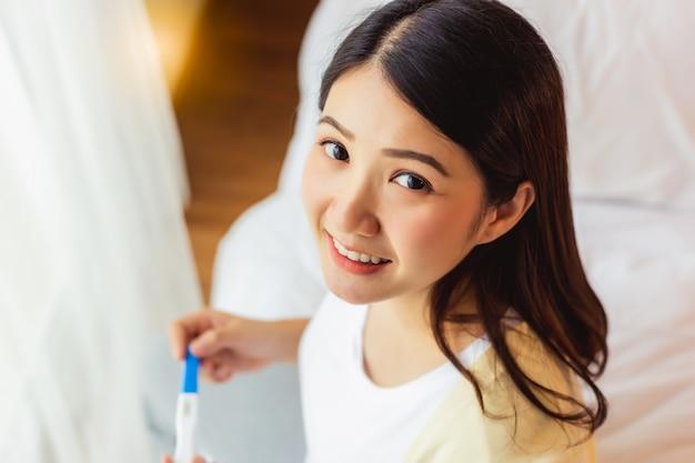 Feliz mujer embarazada con prueba de embarazo y sonriendo