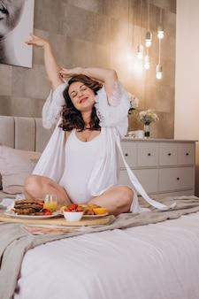 Feliz mujer embarazada en su casa en la cama desayunando