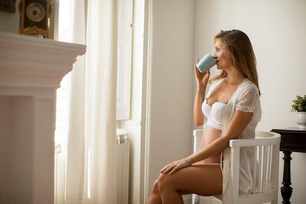 Feliz mujer embarazada con taza de té o leche