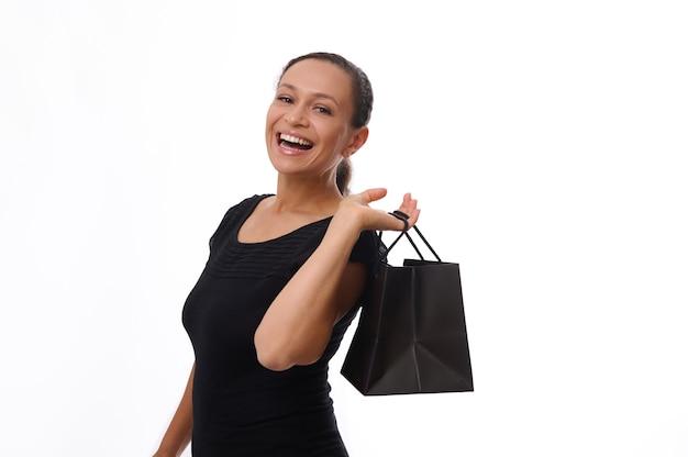 Feliz mujer emocionada vestida con atuendo negro sostiene una bolsa de compras negra y se ríe, sonríe con una hermosa sonrisa con dientes, disfrutando de las compras en el viernes negro, aislado sobre fondo blanco, espacio de copia
