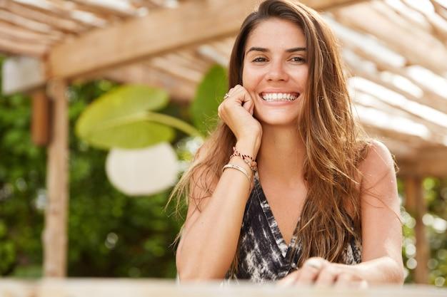 Feliz mujer encantada con larga recta, mantiene la mano debajo de la barbilla, satisfecha con un buen descanso en el país turístico, se sienta en la cafetería al aire libre. feliz joven turista recrear durante las vacaciones de verano