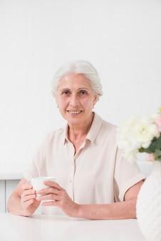 Feliz mujer envejecida sosteniendo una taza de café blanco