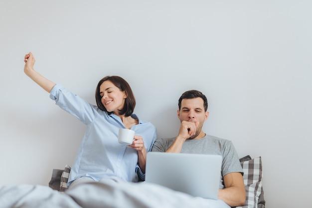 Feliz mujer se estira en la cama, bebe café caliente y su esposo trabaja toda la noche en la computadora portátil