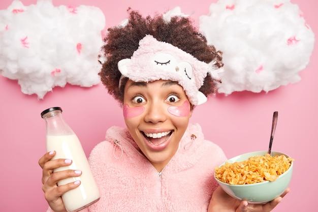 Feliz mujer étnica sorprendida con cabello afro mira con alegría a la cámara sostiene un tazón de cereales con leche viste ropa de dormir te mira positivamente disfruta de un desayuno saludable y procedimientos de belleza