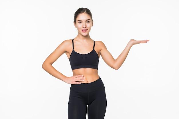 Feliz mujer fitness dedo acusador en copyspace en su palma en una pared blanca