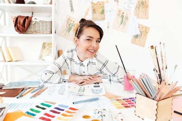 Feliz mujer ilustrador de moda sentado en la mesa