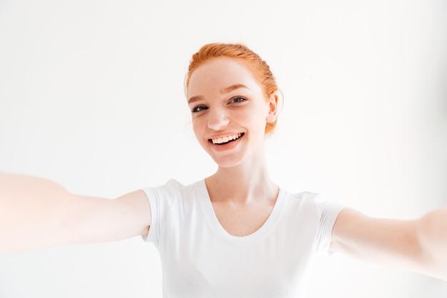Feliz mujer de jengibre en camiseta haciendo selfie y mirando