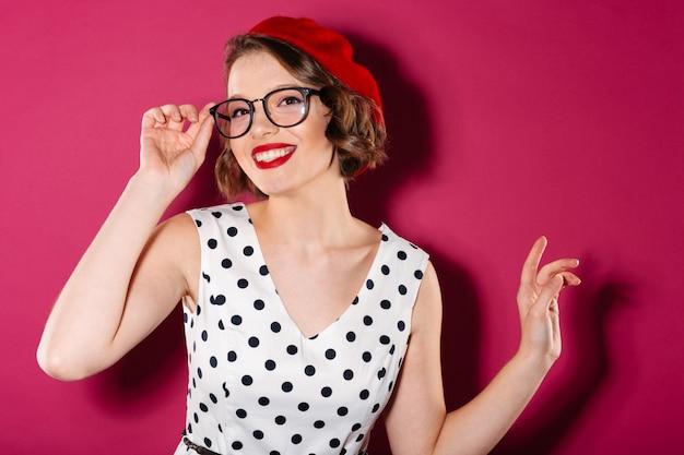 Feliz mujer de jengibre en vestido y anteojos mirando a la cámara sobre rosa