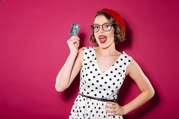 Feliz mujer de jengibre en vestido y anteojos con tarjeta de crédito mientras mira a la cámara sobre rosa