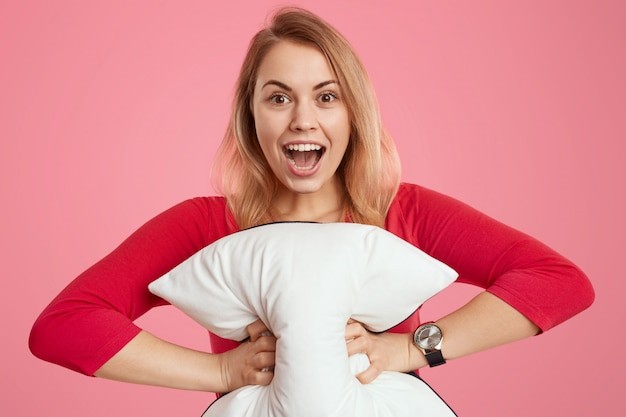 Feliz mujer joven de cabello claro con expresión facial de alegría, sostiene una almohada blanca suave, abre la boca ampliamente