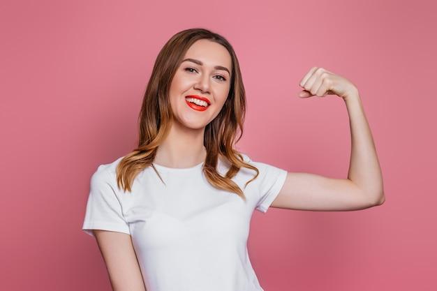 Feliz mujer joven en camiseta blanca sonriendo y muestra sus músculos aislados en la pared rosa.