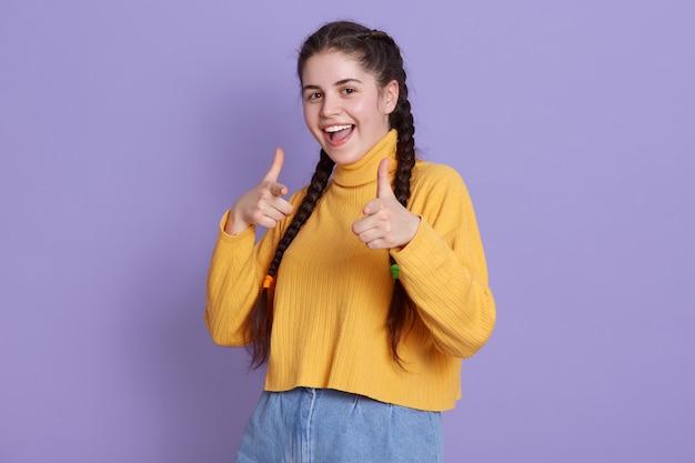 Feliz mujer joven con coletas apuntando con los dedos