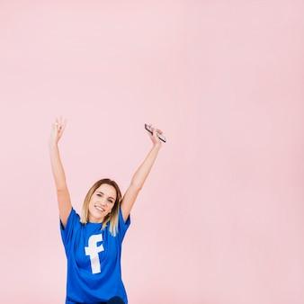 Feliz mujer joven con teléfono móvil levantando los brazos