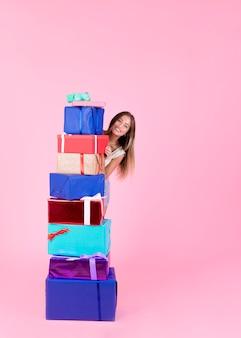 Feliz mujer joven de pie detrás de la pila de cajas de regalo diferentes sobre fondo rosa
