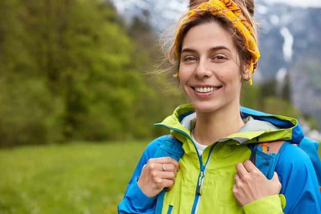 Feliz mujer joven despreocupada posa en la colina de la montaña, sonríe a la cámara