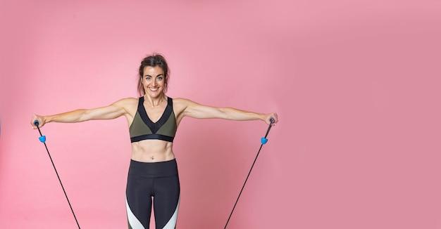 Feliz mujer joven morena con fitness fitness training y haciendo ejercicios de estiramiento con bandas de goma