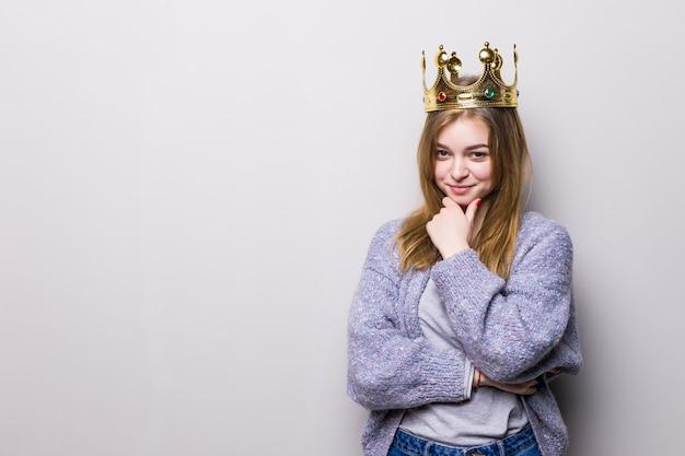 Feliz mujer joven o adolescente en corona de princesa aislada en gris