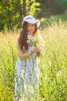 Feliz mujer joven con pelo largo con sombrero y vestido tira de sus manos hacia las plantas mientras camina