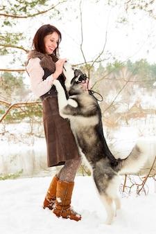 Feliz mujer joven de pie con perro husky siberiano