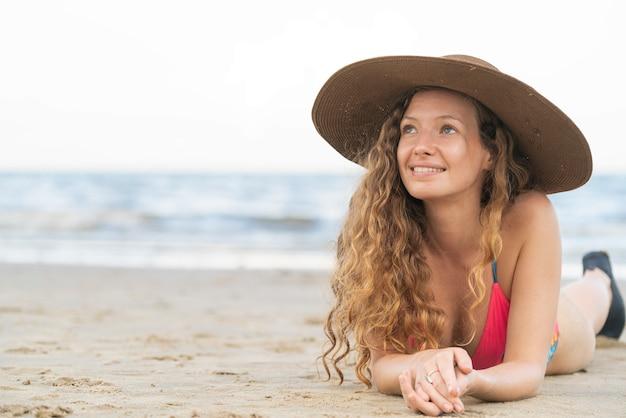 Feliz mujer joven en la playa en vacaciones de verano.