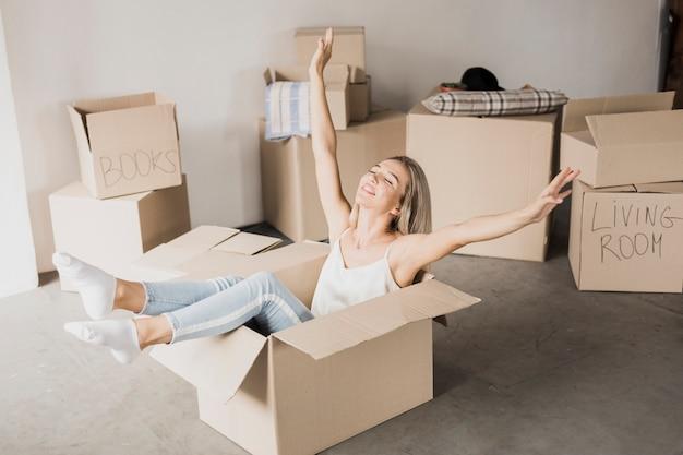 Feliz mujer joven sentada en caja de cartón