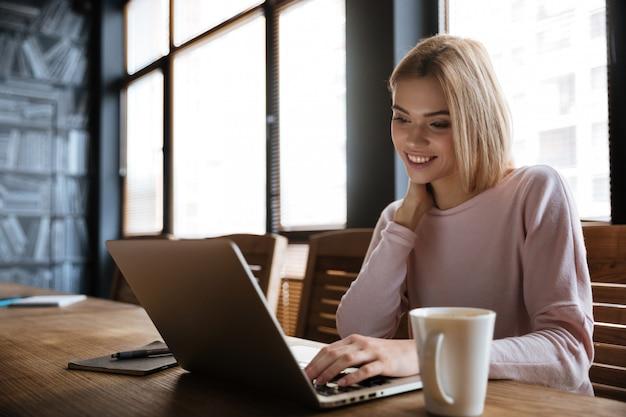 Feliz mujer joven sentada cerca del café mientras trabaja con el portátil
