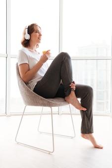 Feliz mujer joven sentada cerca de la ventana bebiendo jugo