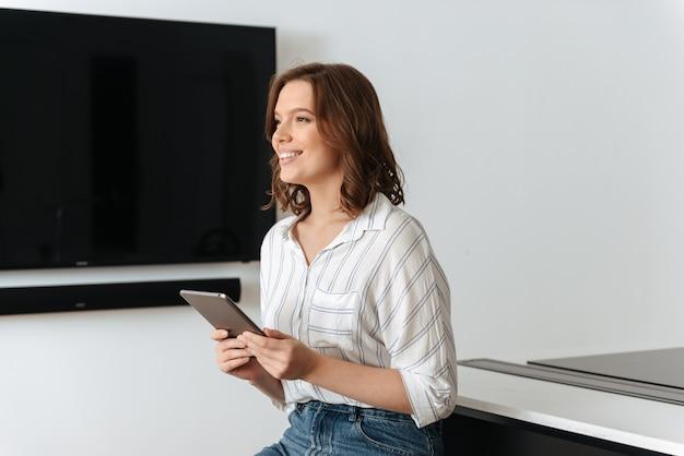 Feliz mujer joven sentada en la cocina en casa, con tablet pc