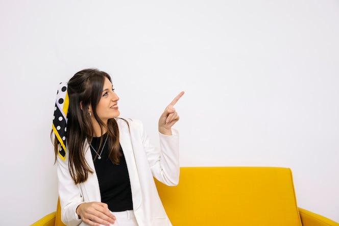 Feliz mujer joven sentada en el sofá amarillo apuntando hacia arriba