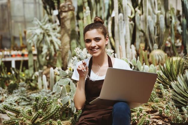 Feliz mujer joven sentada en invernadero usando laptop