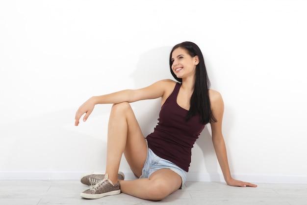 Feliz mujer joven sentada en el piso