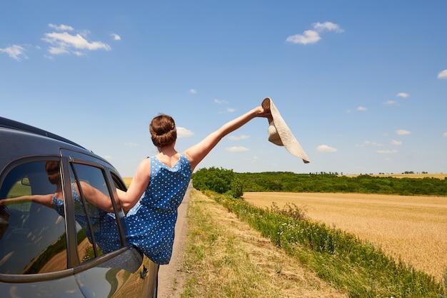 Feliz mujer joven con un sombrero mira por la ventana del coche hacia la carretera.