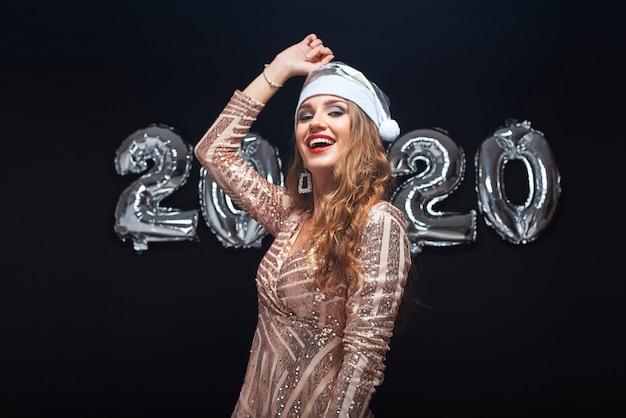 Feliz mujer joven con sombrero de santa divirtiéndose contra globos metálicos 2020.