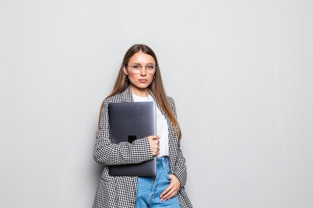 Feliz, mujer joven, tenencia, computador portatil, y, posar