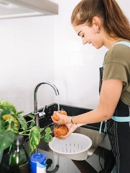 Feliz mujer lavando tomate rojo en el fregadero de la cocina