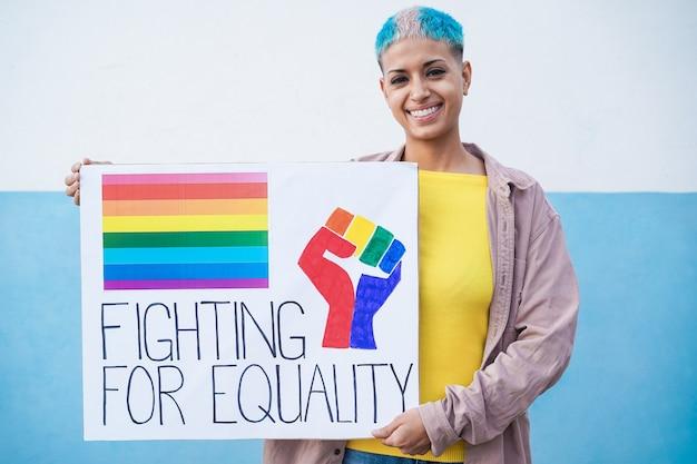 Feliz mujer lesbiana en el desfile del orgullo gay con pancarta lgbt