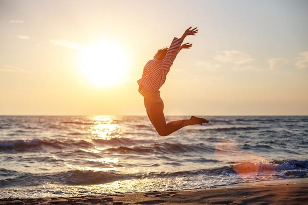 Feliz mujer libre saltando de felicidad en la playa bajo el sol del atardecer