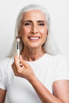 Feliz mujer madura con pincel de maquillaje