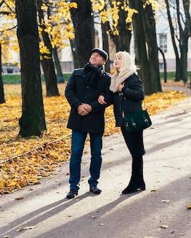 Feliz mujer madura rubia y hermosa morena de mediana edad, mira hacia el cielo, caminando en el parque