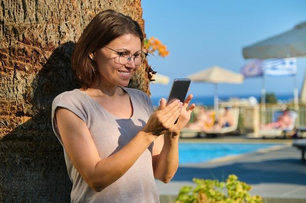 Feliz mujer madura con smartphone. mujer descansando en el resort spa hotel