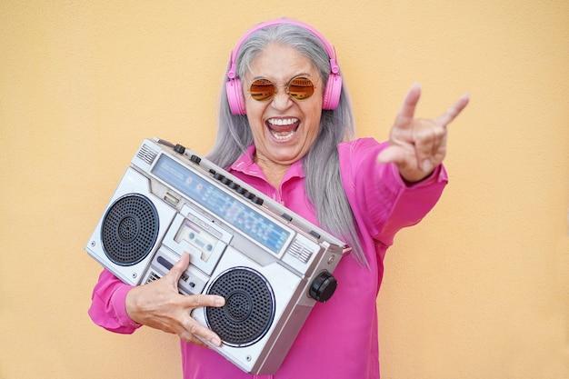 Feliz mujer mayor bailando y sosteniendo estéreo vintage