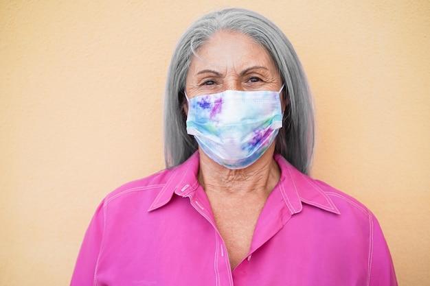 Feliz mujer mayor con máscara protectora