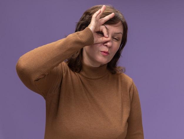 Feliz mujer de mediana edad en cuello alto marrón haciendo el signo de ok mirando a través de este cartel guiñando un ojo de pie sobre la pared púrpura