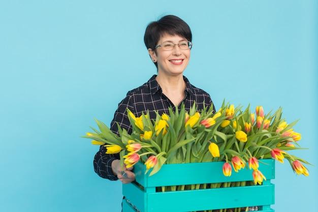 Feliz mujer de mediana edad con gafas sosteniendo una caja de tulipanes en fondo azul.