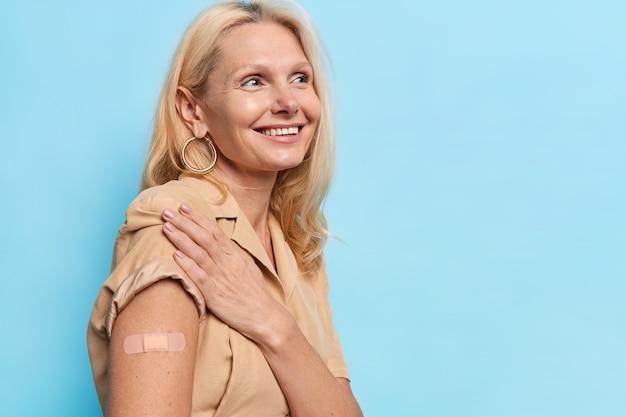 Feliz mujer de mediana edad recibe la inoculación en el hombro se vacuna en la clínica muestra el hombro con vendas adhesivas viste un vestido beige aislado en una pared azul