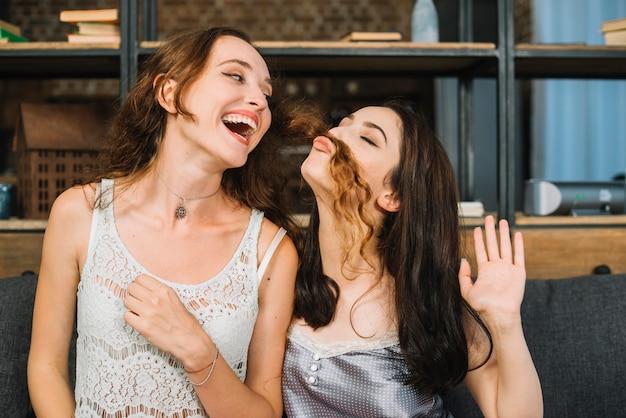 Feliz mujer mirando a su amiga haciendo bigote falso con su pelo