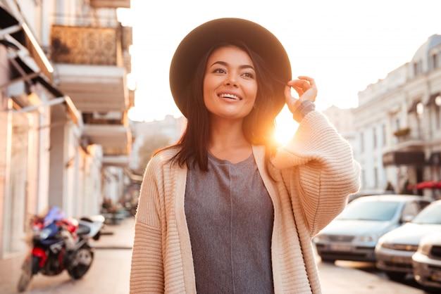 Feliz mujer moda asiática ajustando su sombrero mientras caminaba por la calle de la ciudad